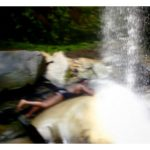 Attempting to plank beneath the falls, and trying not to be swept away...